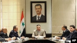 In this undated photo released by the Syrian official news agency on Aug. 5, 2012, Syrian Prime Minister Riad Hijab, center, speaks under the portrait of the Syrian President Bashar Assad during a meeting in Damascus, Syria.