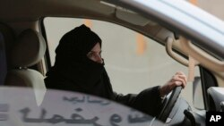 Aziza Yousef drives a car on a highway in Riyadh, Saudi Arabia, as part of a campaign to defy Saudi Arabia's ban on women driving, March 29, 2014. (AP Photo/Hasan Jamali, File)