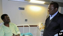 Zimbabwe's Prime Minister Morgan Tsvangirai visits Movement For Democratic Change youth leader Yaya Kassim, attacked while visiting MDC supporters, at a hospital in the capital Harare, August 5, 2011.