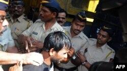 Salah seorang pelaku pemerkosaan, Siraj Rehmat Khan, digiring ke mobil polisi untuk dibawa ke pengadilan di Mumbai (4/4).