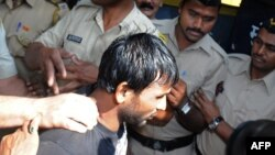 Double gang-rape convict Siraj Rehmat Khan is brought to a police van before taken to court in Mumbai, April 4, 2014.