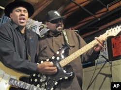 FILE - Blues musicians Ronnie Baker Brooks, left, and his brother, Wayne Baker Brooks, sons of blues legend Lonnie Brooks, perform in their basement in Dolton, Illinois, Feb. 12, 2008.