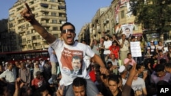 """An Egyptian supporter of Muslim brotherhood candidate Mohammed Morsi wearing a shirt with Arabic that reads, """"'Mohammed Morsi, president for Egypt"""" chants slogans in Tahrir Square, Cairo, Egypt, June 18, 2012."""