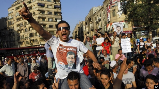 "An Egyptian supporter of Muslim brotherhood candidate Mohammed Morsi wearing a shirt with Arabic that reads, ""'Mohammed Morsi, president for Egypt"" chants slogans in Tahrir Square, Cairo, Egypt, June 18, 2012."