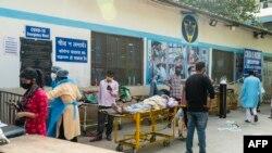 Kerabat menunggu di samping pasien virus corona yang berbaring di tandu di kompleks rumah sakit untuk masuk di New Delhi, 23 April 2021. (Foto: AFP/Maude BRULARD)
