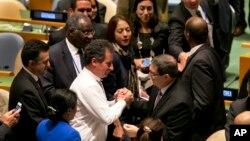 BMTga a'zo davlatlar vakillari Kuba Tashqi ishlar vaziri Bruno Rodrigez Parrillani (markazda) BMT Bosh Assambleyasi qabul qilgan rezolyutsiya bilan tabriklamoqda, 27-oktabr, 2015-yil.