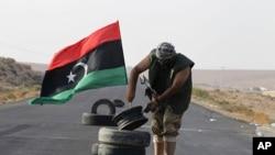 利比亚反政府士兵在通往卡扎菲控制区的最后一个检查站的道路上竖起一面利比亚王国的旗子