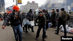 20일 우크라이나 수도 키예프에서 반정부 시위대와 경찰이 또 다시 충돌한 가운데, 시위대가 부상자를 옮기고 있다.
