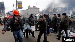 2月20日反政府抗议人士把一名受伤人员抬出基辅的独立广场