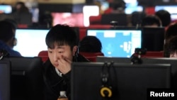 FILE - A man uses a computer at an internet cafe in Hefei, Anhui province, March 16, 2012.