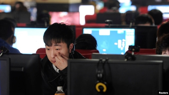 FILE - A man scratches his face as he uses a computer at an internet cafe in Hefei, Anhui province.