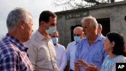 Presiden Suriah Bashar Assad (kedua dari kiri) mengenakan masker saat meninjau provinsi Latakia, Suriah, yang terdampak paling parah akibat kebakaran hutan, 13 Oktober 2020. (Facebook Presiden Suriah via AP).