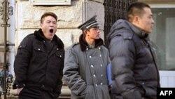 Công an mặc thường phục (trái và phải) canh phía ngoài nhà của nhân vật bất đồng chính kiến đang bị cầm tù Lưu Hiểu Ba