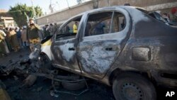 A policeman, background, takes a picture of a damaged car with his cellphone at the scene of a car bombing outside a police academy in Sana'a, Yemen, Jan. 7, 2015.