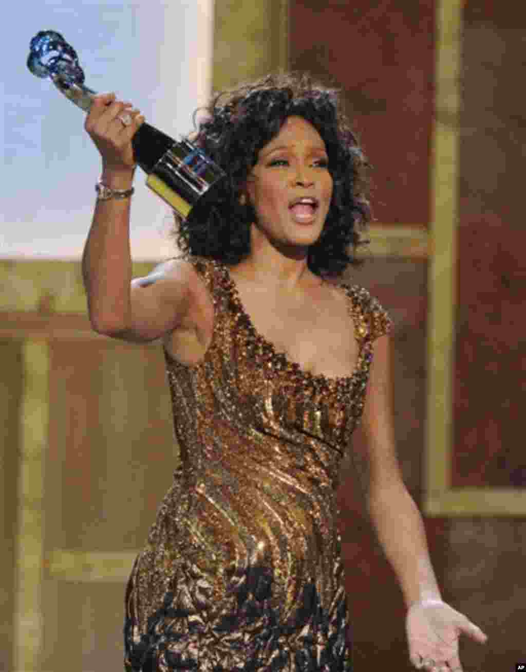 FILE - In this Saturday, Jan. 16, 2010 file photo, Whitney Houston accepts an award at the Warner Theatre during the 2010 BET Hip Hop Honors in Washington. Houston died Saturday, Feb. 11, 2012, she was 48. (AP Photo/Nick Wass)