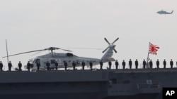 """日本海上自卫队水兵站在最新的护卫舰 """"出云""""号的甲板上接受检阅.(2015年10月15日)"""