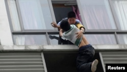 A police officer grabs a man who tries to jump off the 7th floor of a hotel in Chengdu, China. (May 2014)