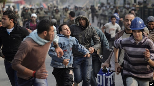 Egyptian protesters run as they are chased by army soldiers over the Asr el-Nile bridge leading out of Tahrir Square, in Cairo, Egypt, Saturday, Dec. 17, 2011.