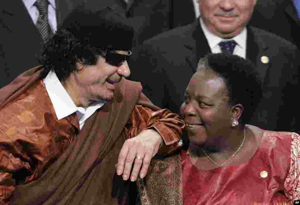 Libyan leader Moammar Gadhafi, left, leans on the shoulder of Pan African Parliament member Gertrude Mongella during a group photo at an EU Africa summit in Lisbon, December 8, 2007. (AP)