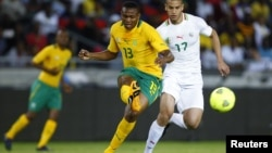 South Africa's Kagisho Dkgacoi (L) is challenged by Algeria's Adlane Guedioura during their international friendly soccer match in Soweto, January 12, 2013, in preparation for the 2013 Africa Cup of Nations.