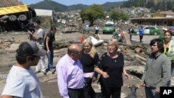 Chile's President Michelle Bachelet (r) talks to residents in a destroyed area of Concepcion, some 100 km (62 miles) south of the epicenter of a huge 8.8-magnitude earthquake that rocked Chile on February 27, 2010.
