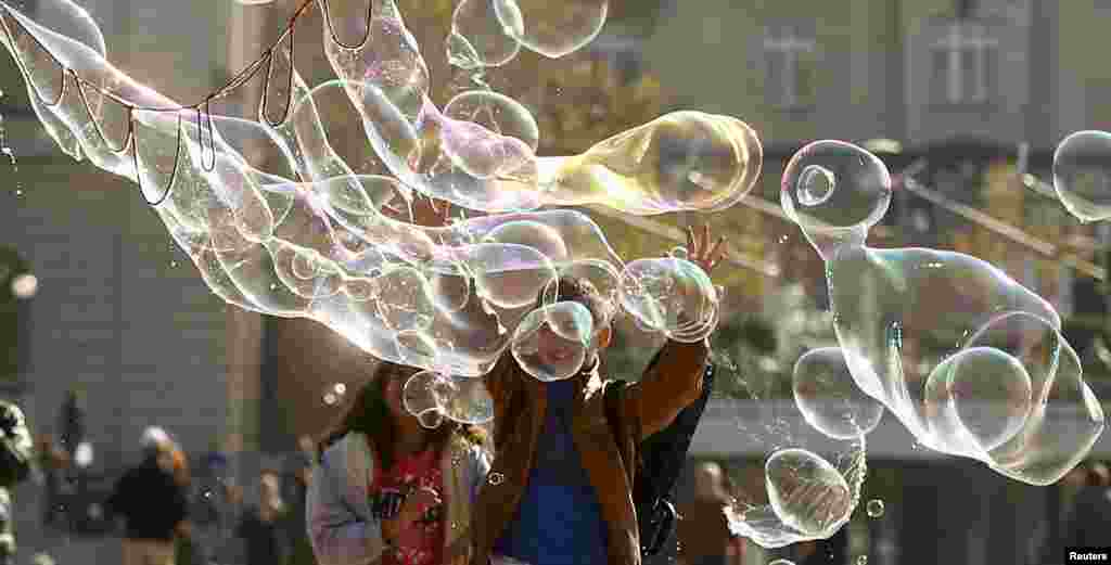 Children try to reach a big soap bubble blown at a square in front of the opera house in Zurich, Switzerland.