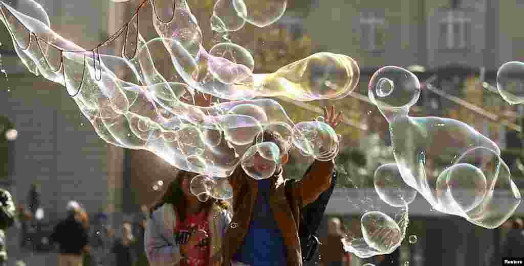 Anak-anak berusaha menyentuh gelembung-gelembung sabun di depan gedungOpera di Zurich, Swiss.