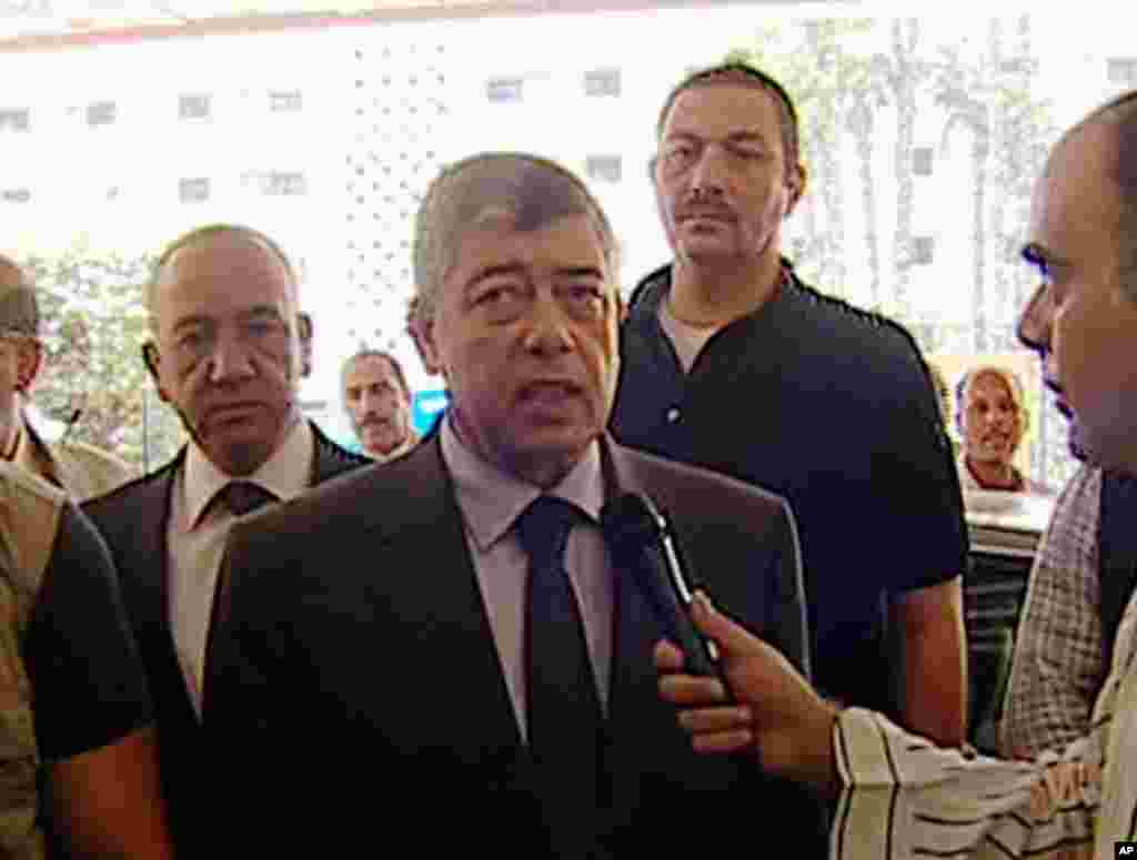 In this image from Egyptian State Television, Egyptian Interior Minister Mohamed Ibrahim responds to a reporter after an explosion near his convoy in Cairo, Sept. 5, 2013.