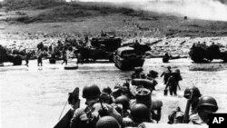 Kamioni-amfibije i pripadnici pešadije izlaze na obalu na početku invazije na Francusku, 6. juna 1944.