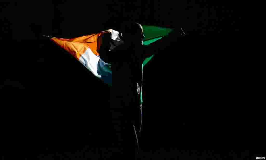 Gold medallist Katie Taylor of Ireland carries her country's flag during the presentation ceremony for the Women's Light (60kg) boxing competition.