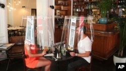 A man and a woman demonstrate dining under a plastic shield Wednesday, May 27, 2020 in a restaurant of Paris. (AP Photo/Thibault Camus)