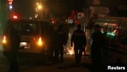 Des véhicules de police devant des pneus brûlés par des manifestantsà Tunis le 9 janvier 2018.