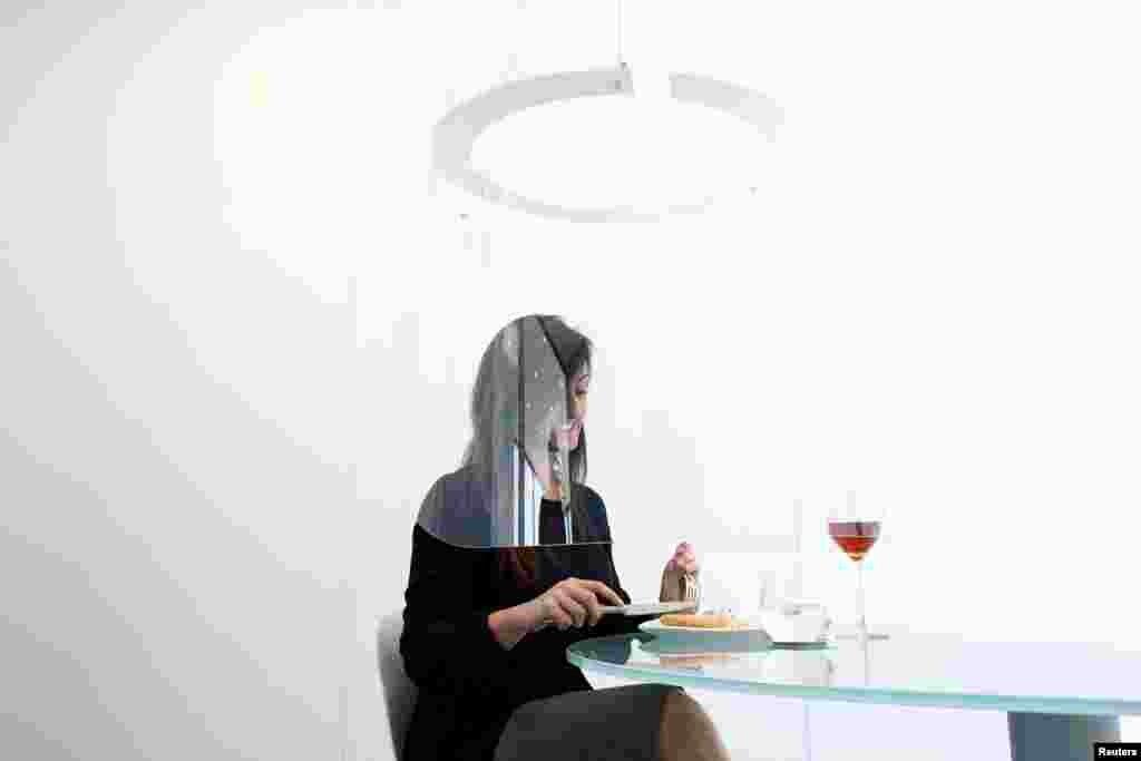 ស្ត្រីម្នាក់អង្គុយនៅក្រោមគំរូទីមួយនៃកញ្ចក់Plex'Eat រៀបចំឡើងដោយអ្នករចនាម៉ូតChristophe Gernigon ដែលកញ្ចក់នេះព័ទ្ធជុំវិញអាហារពេលល្ងាច ដើម្បីការពារការចម្លងវីរុសកូរ៉ូណា ក្នុងពេលមានការបង្ហាញមួយនៅទីក្រុងCormeilles-en-Parisis ក្បែរទីក្រុងប៉ារីស ប្រទេសបារាំង។