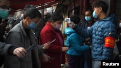 雲南昆明民眾戴著口罩拿著手機進行個人健康掃碼方能進入超市購物。 (2020年2月24日)