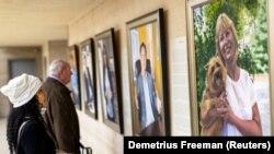 "Visitors examine Artist Betsy Ashton's exhibition, ""Portraits of Immigrants"""