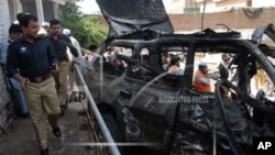 Pakistani police officers visit the site of an explosion in Peshawar, Pakistan on Friday, May 24, 2013. Police say a suicide bomber walked up to a vehicle owned by an Afghan religious leader in northwestern Pakistan and set off his explosives, killing sev