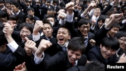 Japanese college students shout and raise their fists during a pep rally held to boost their morale ahead of their job hunt, at an outdoor theatre in Tokyo February 25, 2016.