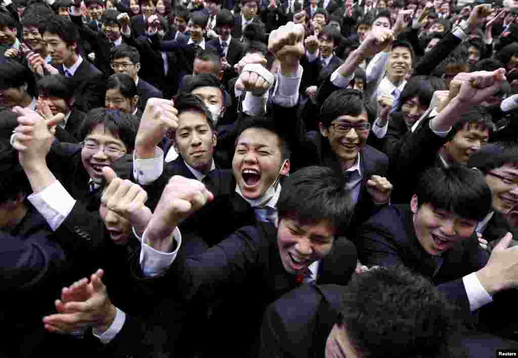 Japanese college students shout and raise their fists during a rally held to boost their morale ahead of their job hunt, at an outdoor theater in Tokyo.
