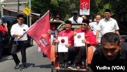 Pasangan bakal calon yang diusung PDIP Solo diarak menggunakan becak saat mendaftar di kantor DPC PDI P Solo, Senin (23/9). (Foto: VOA/ Yudha Satriawan)