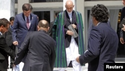 Afghan President Hamid Karzai (C) arrives for a group photo with the foreign attendees of the Asia Ministerial Conference in Kabul, June 14, 2012.