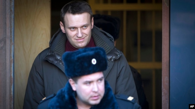 Russian opposition activist Alexei Navalny, surrounded by police officers, leaves a court after being sentenced to seven days in prison for participating in an anti-government protest in Moscow, Feb. 25, 2014.