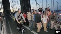 """Biciklisti prolaze pored glumaca """"zombija"""" na Bruklinškom mostu u Njujorku."""