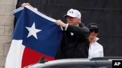 رئیس جمهوری آمریکا در سفر به تگزاس پس از توفان پرچم این ایالت را در دست دارد.