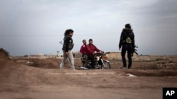 Kurdish female members of the Popular Protection Units check identifications of Kurdish men on a motorbike at a check point near the northeastern city of Qamishli, Syria, March 3, 2013.