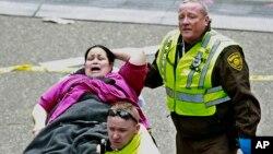 医疗救护人员在波士顿马拉松终点线附近救助一名受伤的女士。