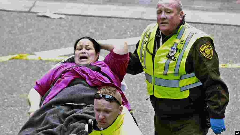 Medical workers aid a wounded woman at the finish line of the 2013 Boston Marathon following two explosions there, April 15, 2013.
