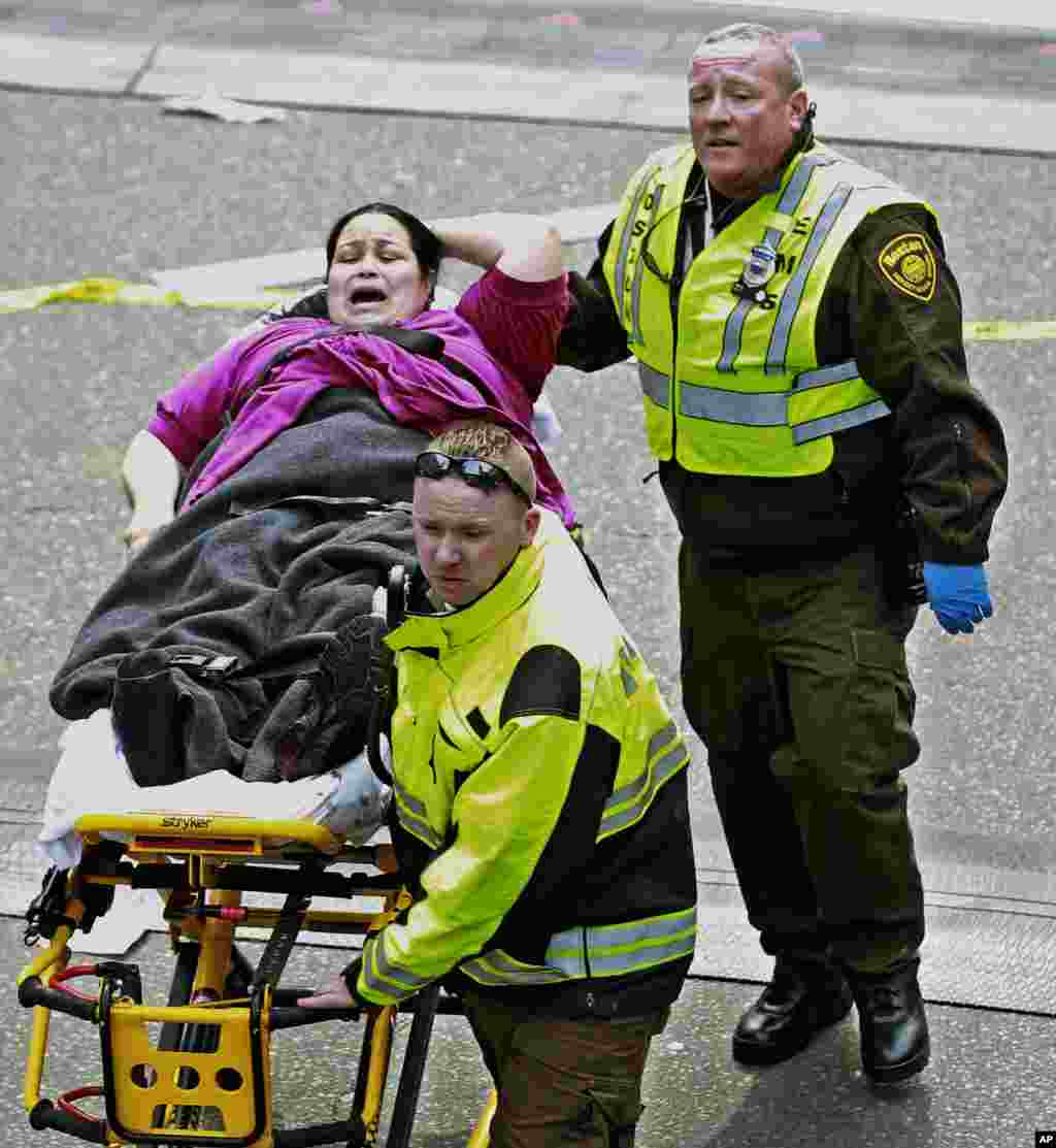 Medical workers aid an injured woman at the finish line of the 2013 Boston Marathon following two explosions there, April 15, 2013.