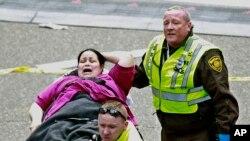 醫療急救人員在波士頓馬拉松終點線附近救助一位受傷的女士。