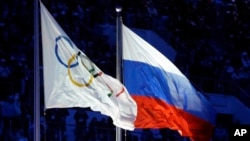 FILE - The Russian and the Olympic flags wave during the opening ceremony of the 2014 Winter Olympics in Sochi, Russia, 7, 2014.