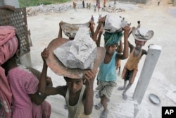 FILE - Child laborers carry stones on their head at a stone crusher on the outskirts of Gauhati, India, June 11, 2008.